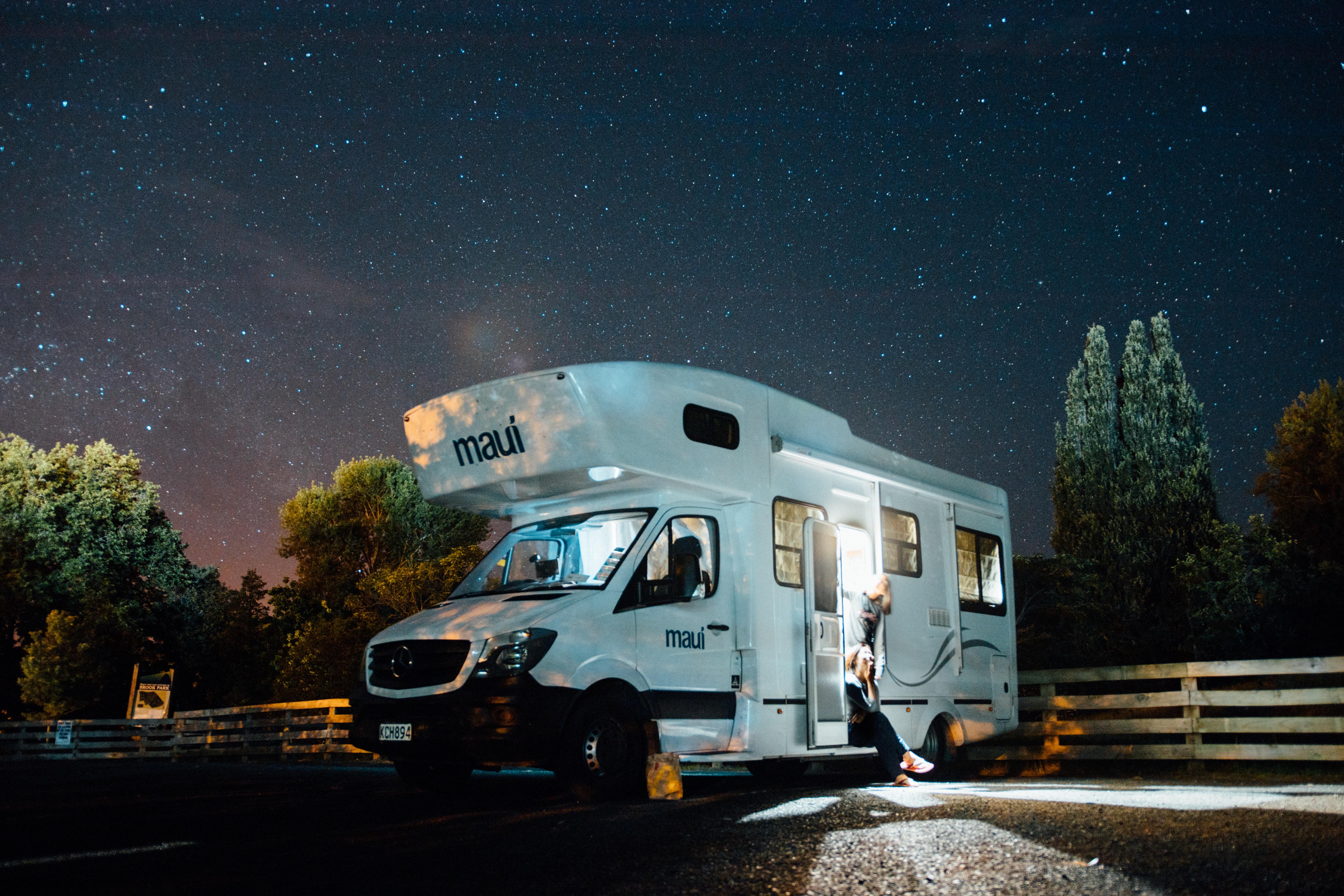 Un camper con due persone sotto un cielo stellato
