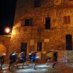 Atleti che corrono in un borgo toscano