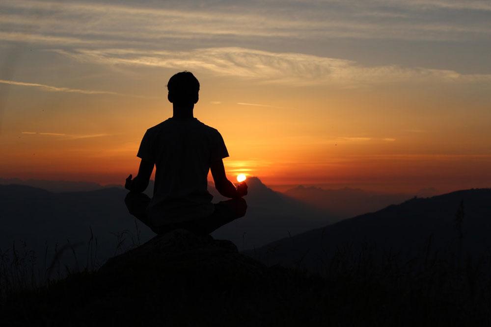 Un uomo che fa Yoga al tramonto