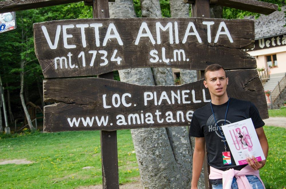 Un ragazzo sotto un cartello che indica l'altezza della Montagna