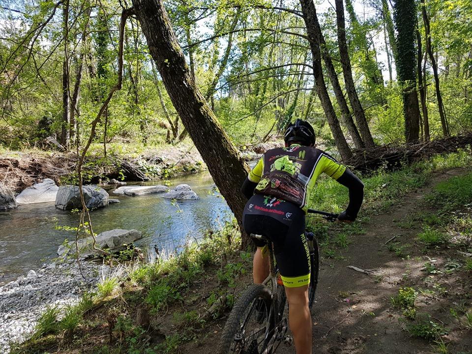 Un ciclista che si allena lungo le rive di un torrente